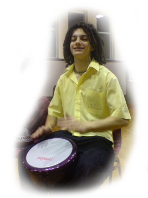Oliver Parker enjoying a school drumming workshop playing along with a hand drum.